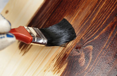 Brush applying stain to wood